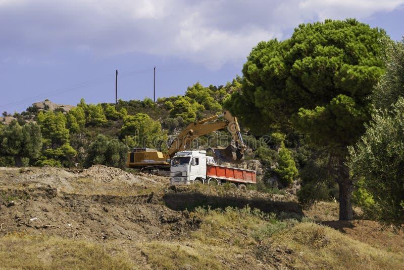 A máquina escavadora amarela no canteiro de obras carrega o solo no corpo de um caminhão basculante vermelho foto de stock