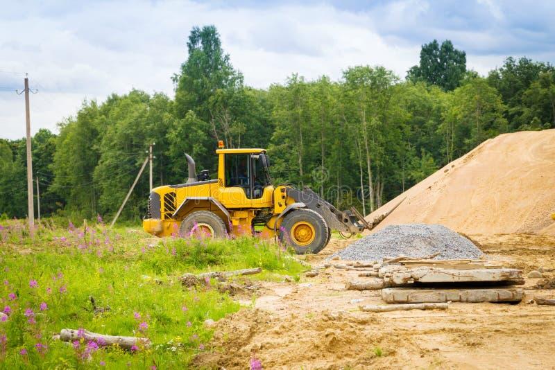 Máquina escavadora amarela no trabalho imagem de stock