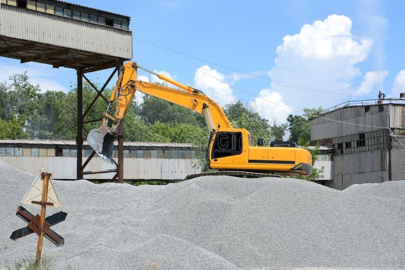 A máquina escavadora amarela recolhe a entulho de uma grande pilha na cubeta e derrama-a no caminhão fotografia de stock royalty free