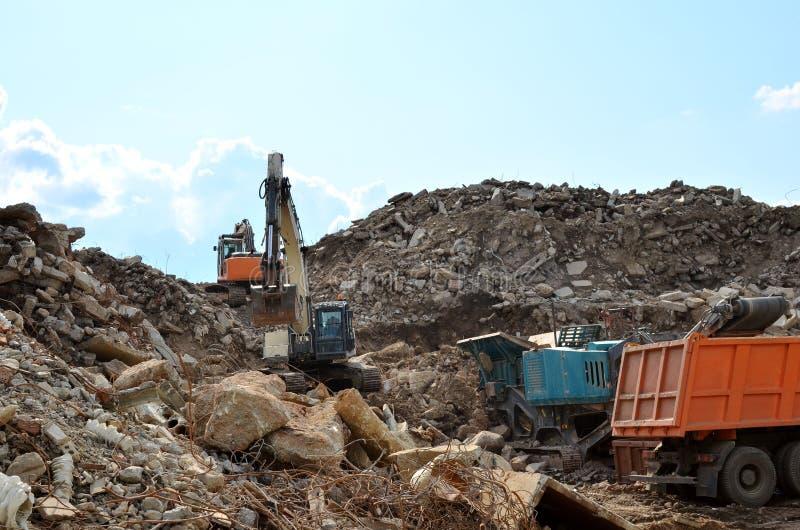 A máquina escavadora carrega o desperdício da construção na retalhadora móvel concreta reforçada para esmagar, reciclagem de desp imagem de stock royalty free