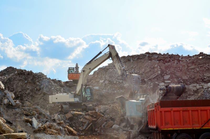 A máquina escavadora carrega o desperdício da construção na retalhadora móvel concreta reforçada para esmagar, reciclagem de desp fotos de stock royalty free