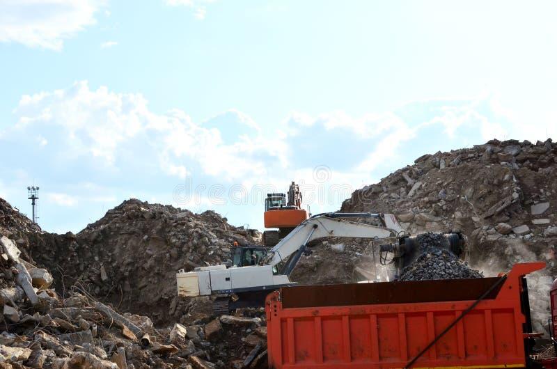 A máquina escavadora carrega o desperdício da construção na retalhadora móvel concreta reforçada para esmagar, reciclagem de desp fotografia de stock
