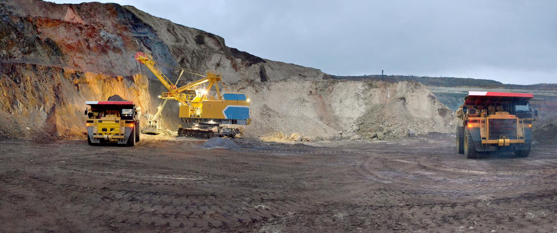 A máquina escavadora carrega a rocha no descarregador fotos de stock