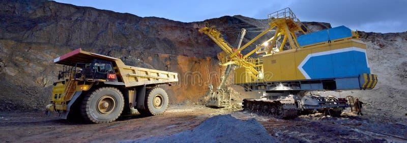 A máquina escavadora carrega a rocha no descarregador imagens de stock royalty free