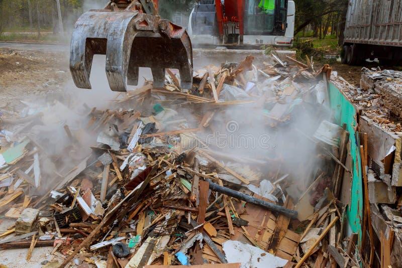 a máquina escavadora desmonta casa quebrada após a tragédia imagem de stock