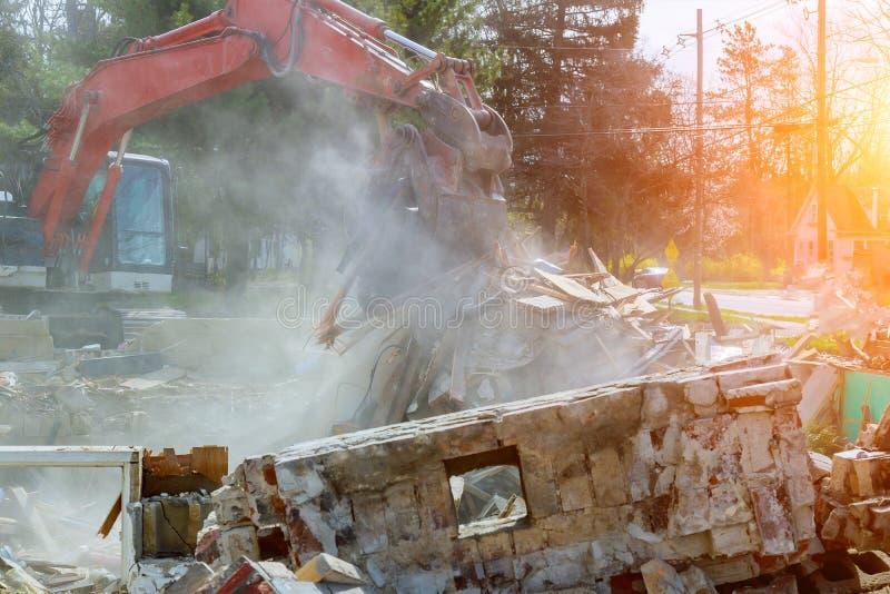a máquina escavadora desmonta casa quebrada após a tragédia fotos de stock