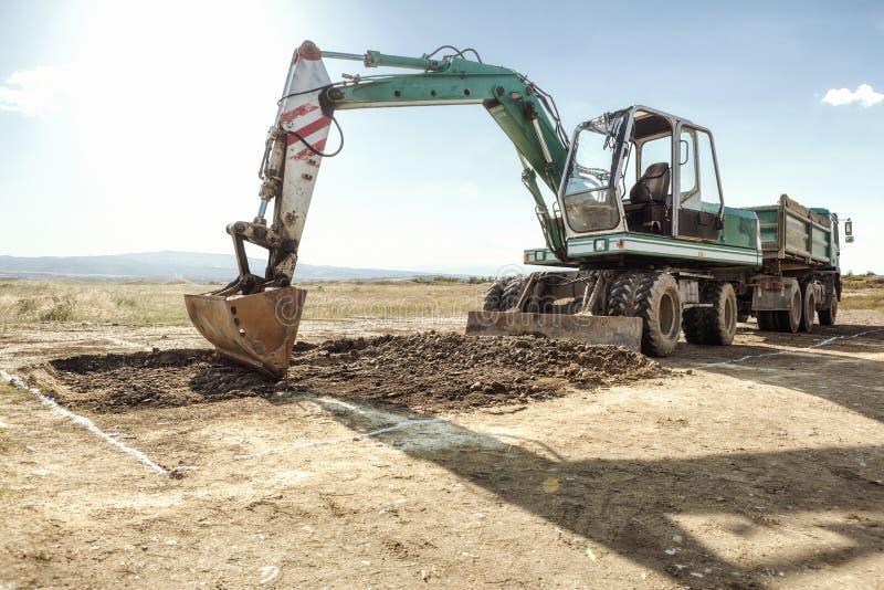 Máquina escavadora e caminhão em um canteiro de obras imagens de stock