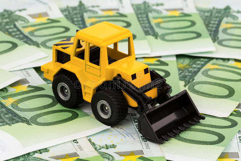 Máquina escavadora em euro- cédulas fotografia de stock