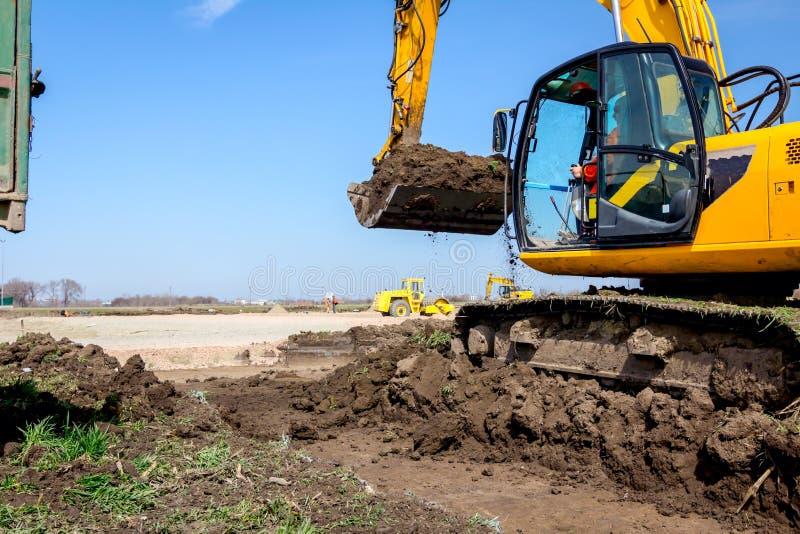 A máquina escavadora está carregando um caminhão com a terra no terreno de construção imagem de stock royalty free
