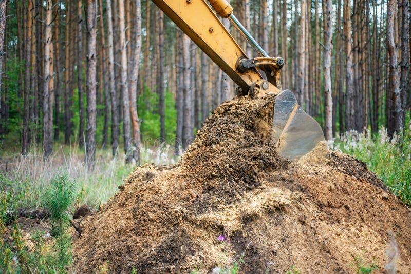 A máquina escavadora executa o trabalho da escavação escavando a terra com uma cubeta fotos de stock royalty free