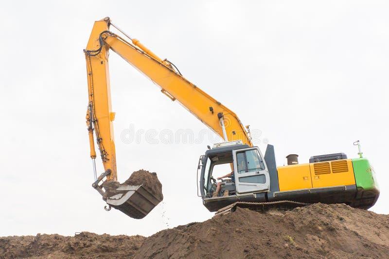 A máquina escavadora faz a barreira do ruído com solo arenoso fotografia de stock royalty free