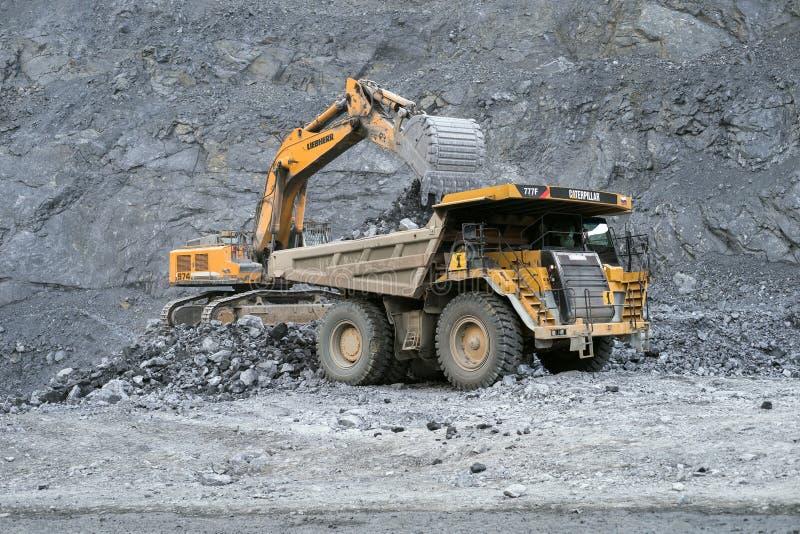 A máquina escavadora Liebherr carrega o minério em um caminhão basculante Caterpillar no fundo de uma pedreira foto de stock