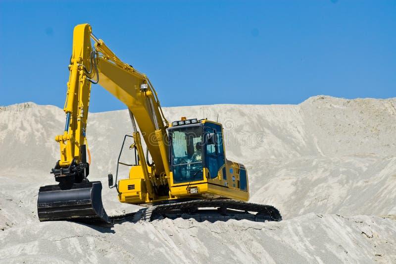 Máquina escavadora na areia imagem de stock