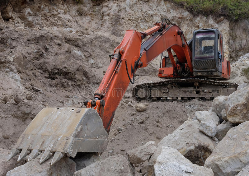Máquina escavadora nas pedras fotos de stock