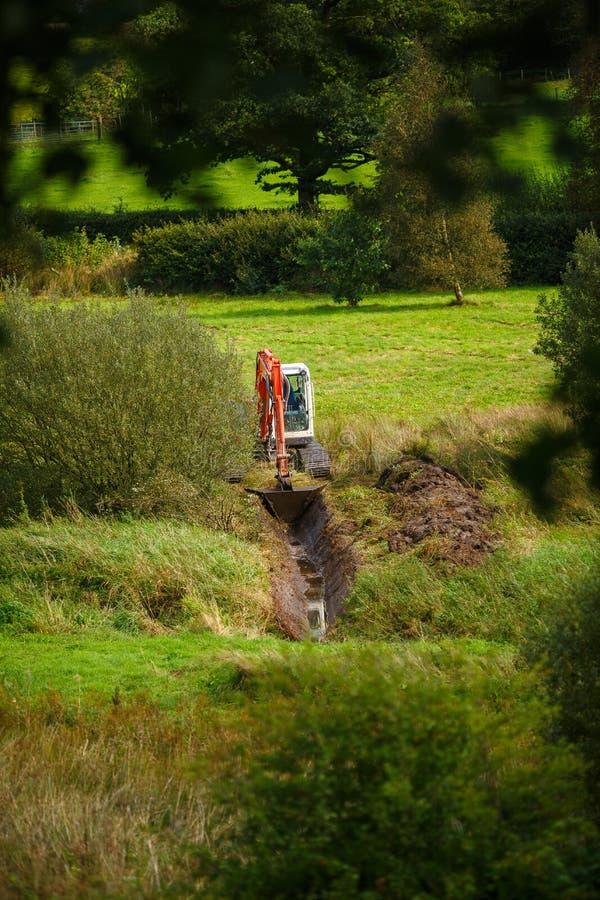Máquina escavadora no campo foto de stock