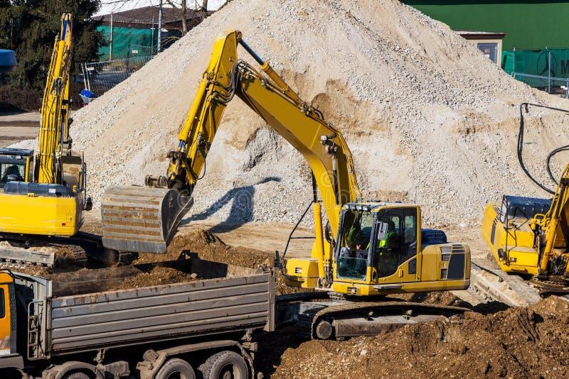 Máquina escavadora no canteiro de obras durante a escavação fotografia de stock royalty free