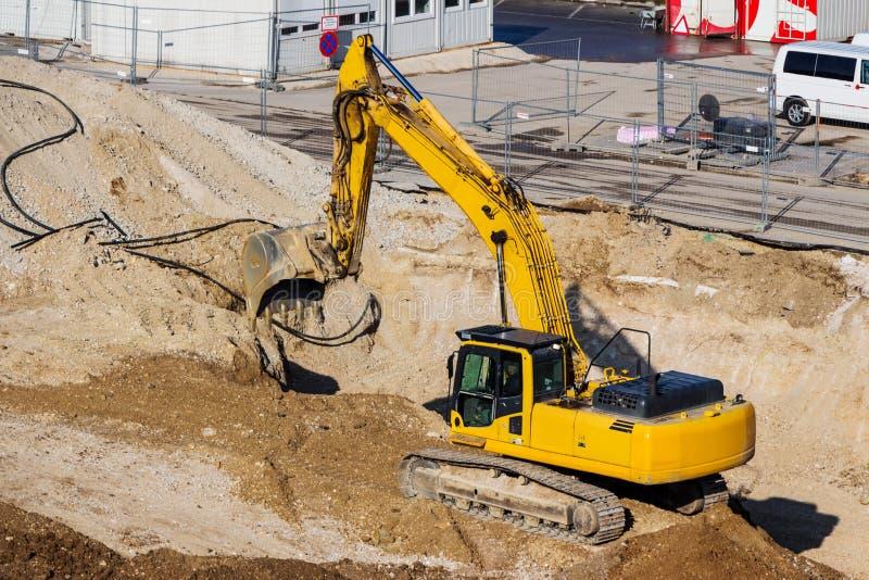 Máquina escavadora no canteiro de obras durante terraplenagens imagens de stock royalty free