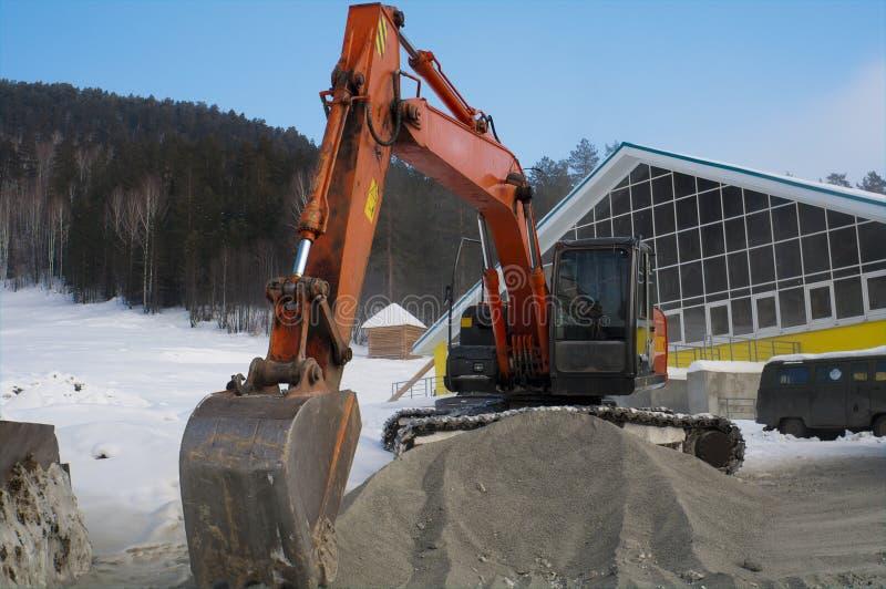 Máquina escavadora perto de uma pilha da entulho foto de stock royalty free