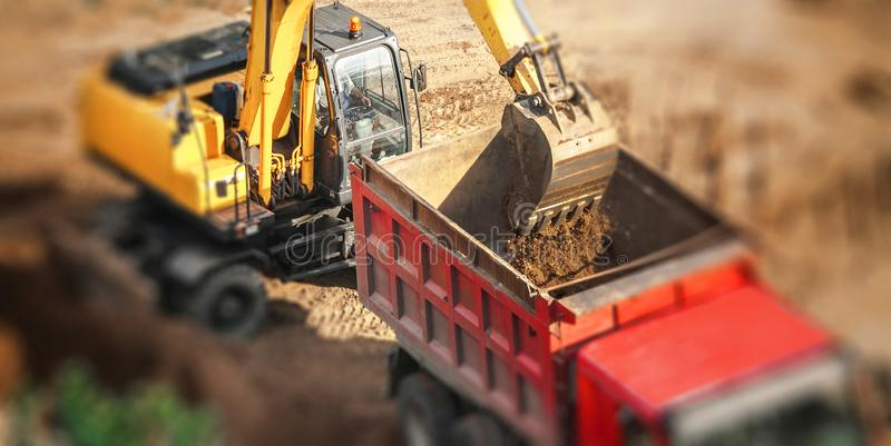 Máquina escavadora que carrega o caminhão de descarregador fotografia de stock royalty free