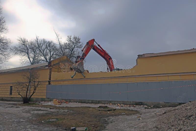 Máquina escavadora que demole uma parede de construção imagem de stock royalty free