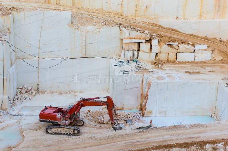 Máquina escavadora que escava na pedreira de mármore foto de stock