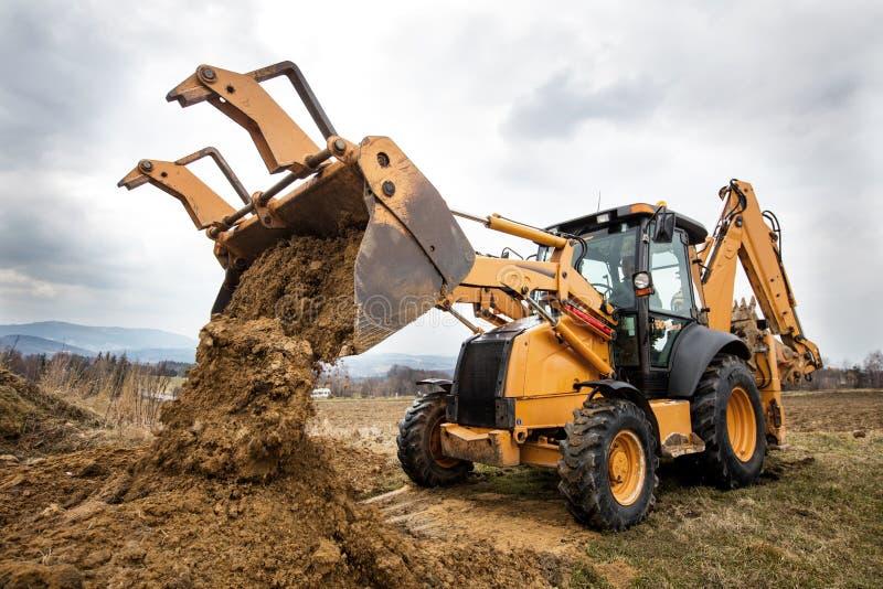 Máquina escavadora que faz terraplenagens no local imagens de stock royalty free