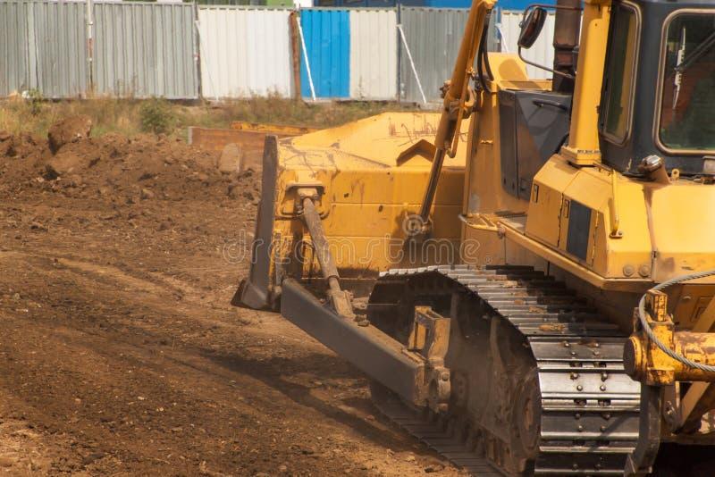 Máquina escavadora que trabalha em um canteiro de obras Escavadora amarela da construção no trabalho Construção de uma estrada no imagem de stock