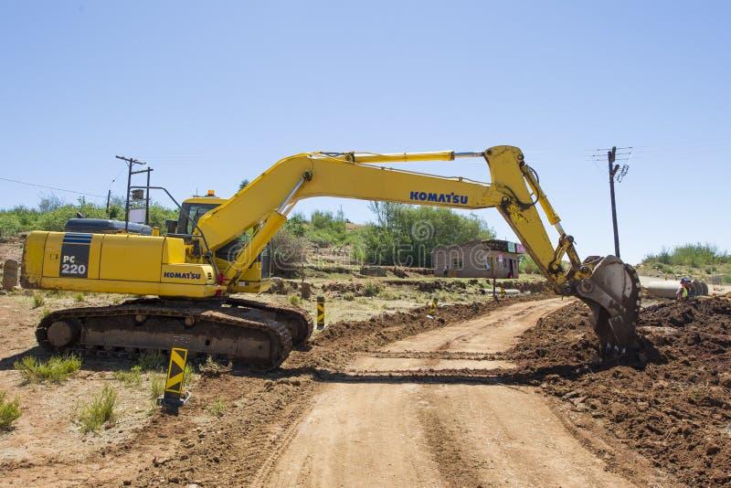 Máquina escavadora que trabalha na estrada imagem de stock