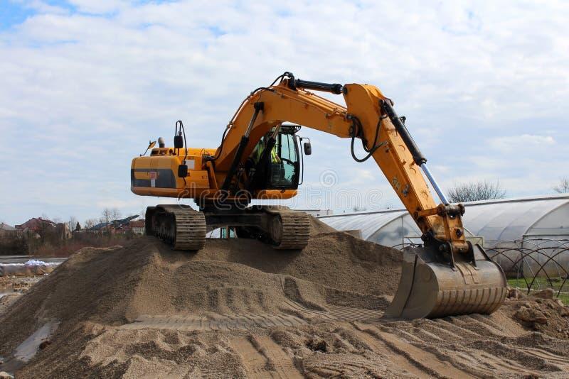 Máquina escavadora sobre a pilha da areia fotografia de stock royalty free