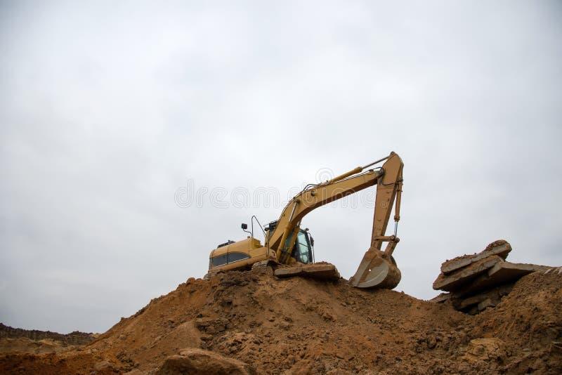 Máquina excavadora de naranjas en losas de tierra en el lugar de construcción Backhoe desentierra el terreno para construir la fu imagen de archivo
