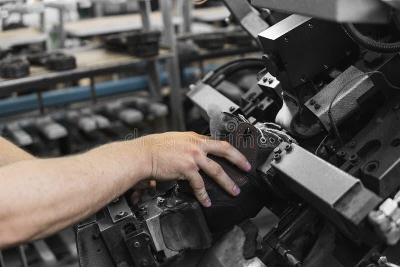 Máquina-herramienta especial del uso del hombre para hacer los zapatos El transportador en una fábrica de zapatos con el zapato y fotos de archivo libres de regalías