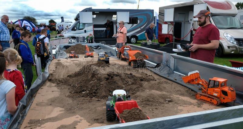 Máquina modelo e caminhões de escavação que estão sendo demonstrados na mostra foto de stock