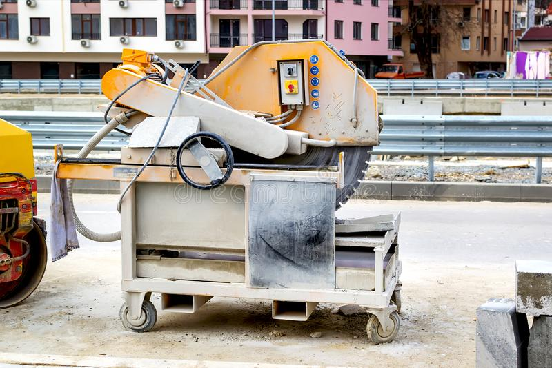 Máquina para cortar pavimentos no local da construção de estradas em uma rua da cidade Maquinaria do Road-building Melhoria de ur fotos de stock