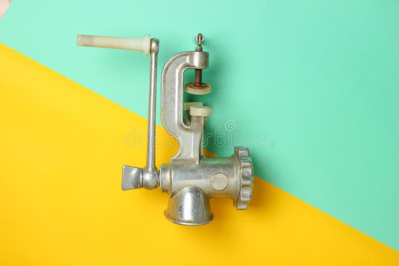 Máquina para picar carne en un fondo en colores pastel, visión superior, minimalismo del vintage foto de archivo libre de regalías