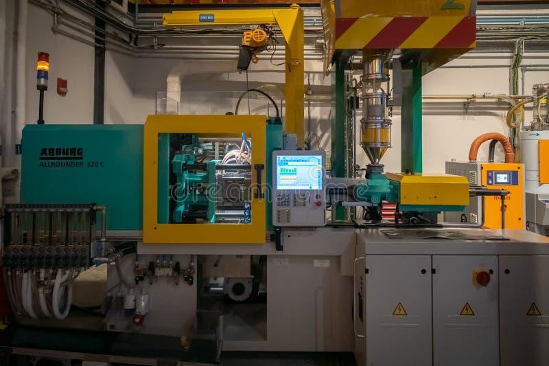 Máquina plástica del moldeo a presión en curso de crear un ladrillo Lego en Legoland foto de archivo