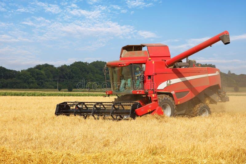 Máquina segador en el campo de trigo, cosechando imágenes de archivo libres de regalías