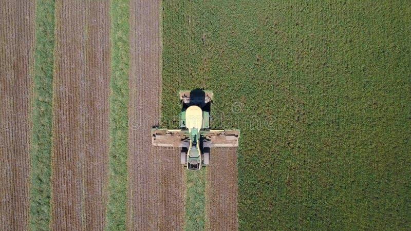 Máquina segadora en un campo verde fotografía de archivo