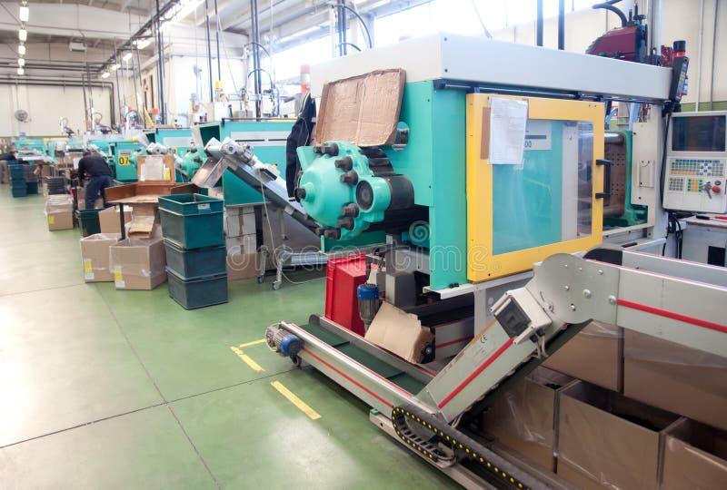 Máquinas da modelação por injecção em uma grande fábrica imagens de stock