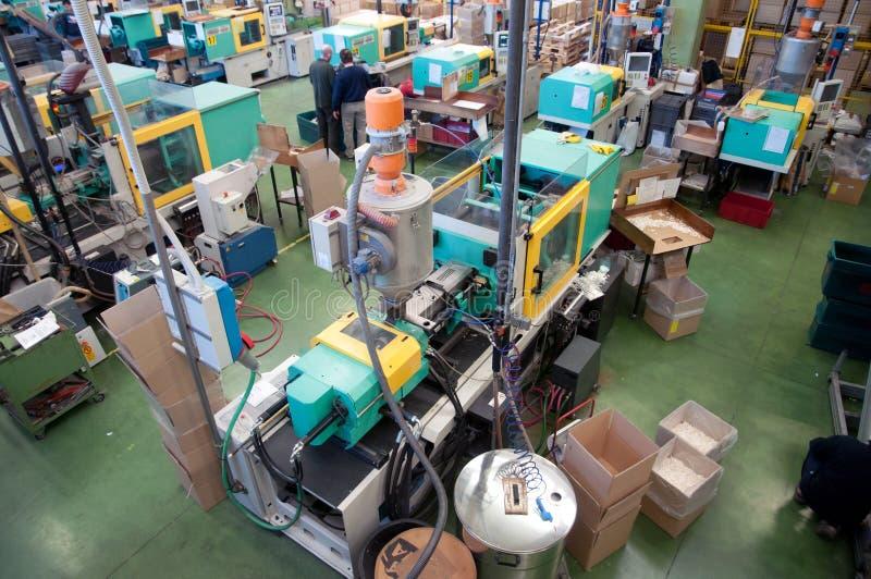 Máquinas da modelação por injecção em uma grande fábrica imagem de stock