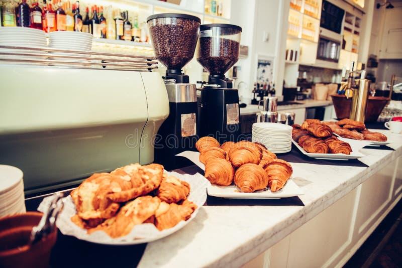 Máquinas del café con las habas y panadería fresca de los cruasanes y de los bollos en las placas en la barra del café para el de imágenes de archivo libres de regalías