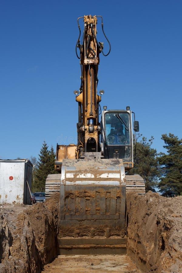 Máquinas escavadoras que escavam a trincheira do esgoto imagens de stock royalty free