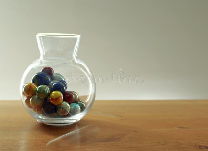 Mármores coloridos em um frasco de vidro em um tampo da mesa fotografia de stock