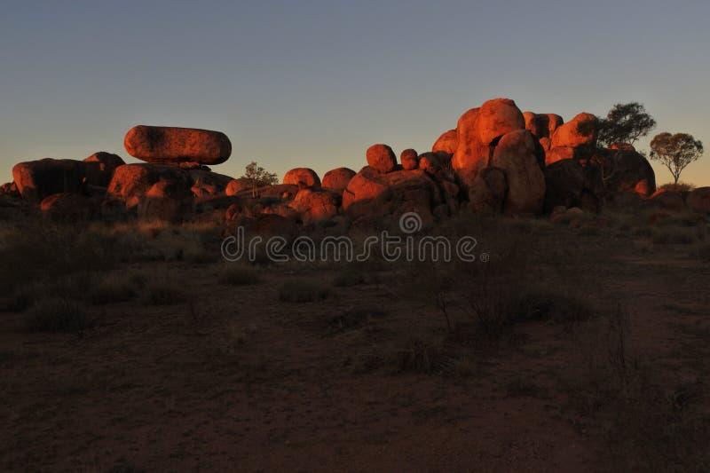 Mármores Karlu Karlu dos diabos no por do sol no Território do Norte, Austrália fotos de stock royalty free