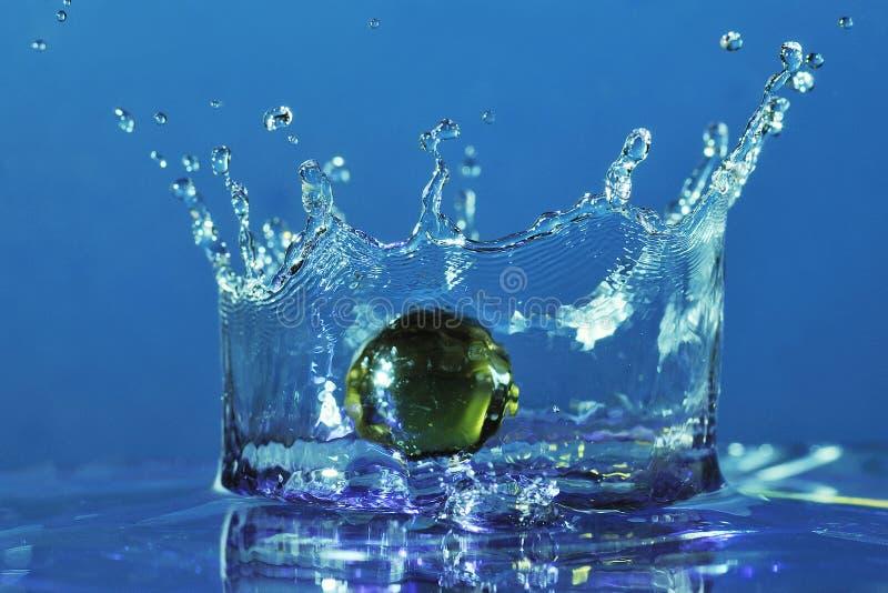 Mármores que caem na água. fotografia de stock