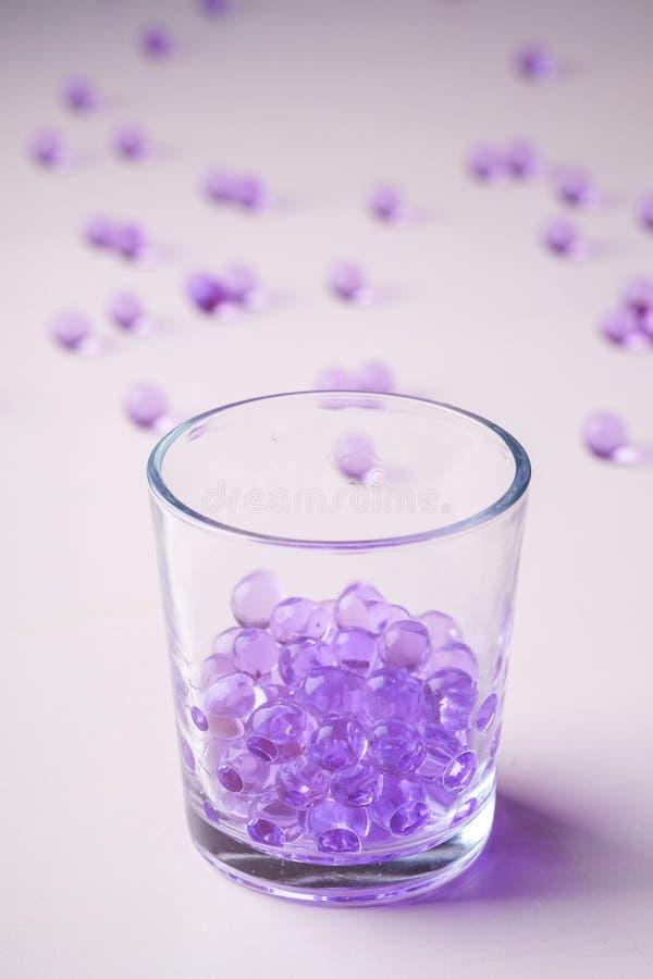 Mármores roxos em beber o vidro transparente com mármores dispersados no fundo branco fotografia de stock royalty free