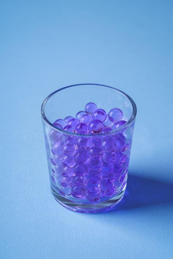 Mármores roxos em beber a opinião de ângulo azul de vidro transparente do fundo fotos de stock royalty free