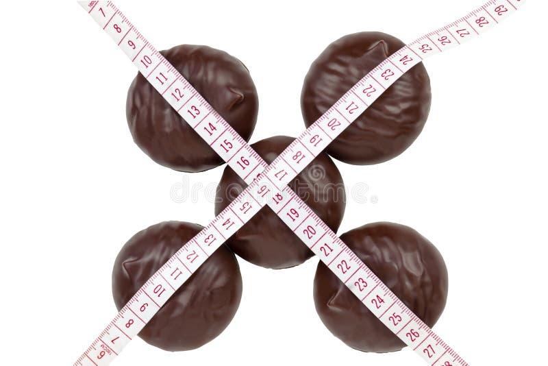 Márshmallows de chocolate com fita métrica sobre fundo branco Fechamento imagem de stock