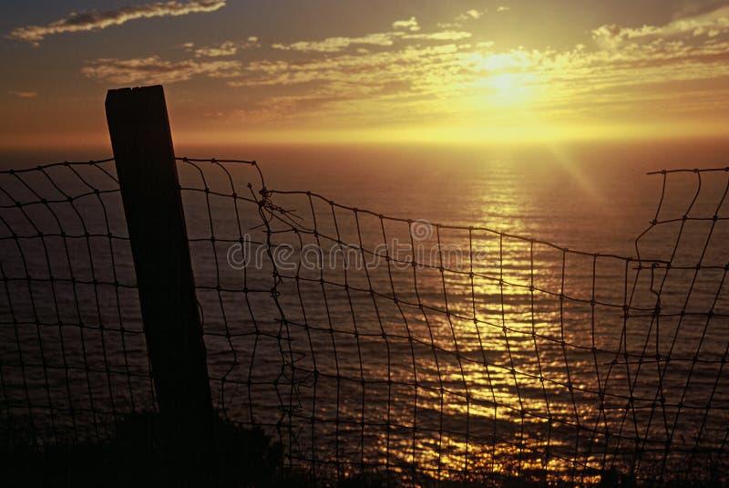 Más allá de las cercas: Puesta del sol de la costa de Caiformia foto de archivo