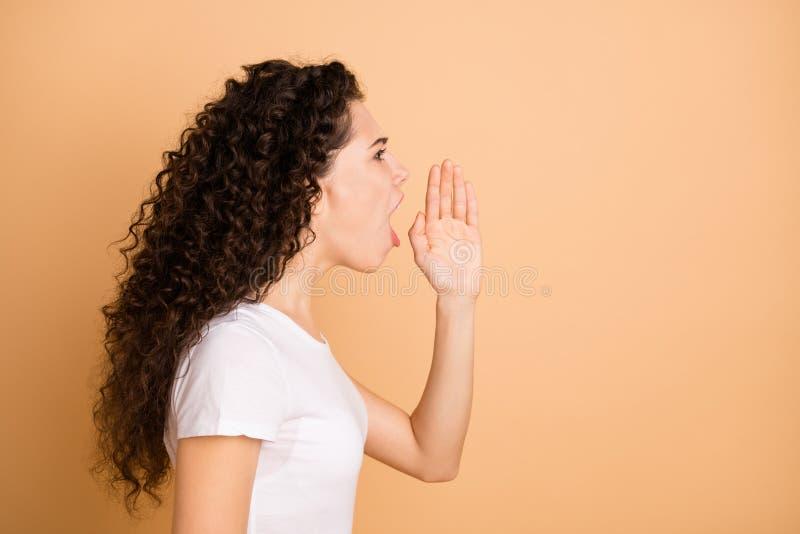 Más notícias Foto do perfil de uma senhora bonita gritando raiva forte para o espaço vazio segurando a mão perto da boca usando c foto de stock royalty free