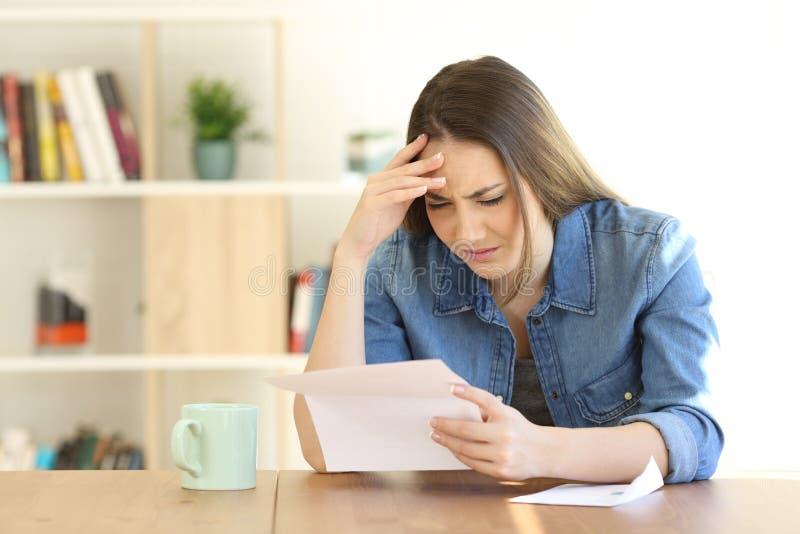 Más notícias preocupadas da leitura da mulher em uma letra fotos de stock